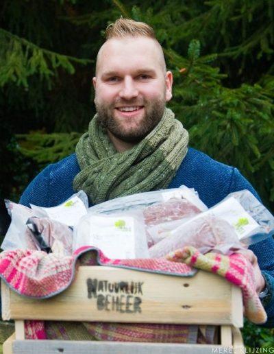Online Biologisch vlees bestellen. Sieger poseert met een zelfgemaakt kistje gemaakt door medewerker bij Phusis